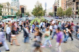 city scene with many people crossing at a pedestrian crossing zone