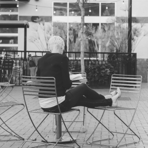 Cristen Iris sitting outside on metal chair in downtown Boise setting with back to the camera reading
