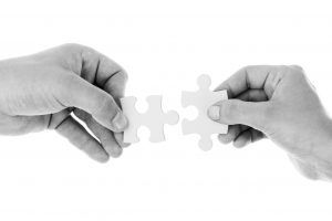 close-up of two hands each with a puzzle piece moving toward each other to make the fit