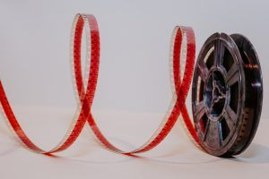 celluloid film reel against a white background, some film unspooled