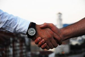 closeup of two people's hands clasped in a handshake against a cityscape
