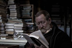 older man reading in a dim room full of stacked books