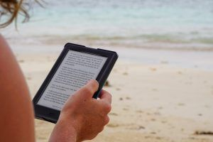 person on beach with an e-reader
