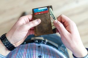 close-up of a man pulling money out of a wallet