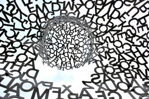 jumbled letters (black on white) coming together in the middle to form a circle but no clear meaning