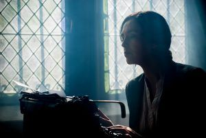 woman sitting at a typewriter in front of leaded glass windows