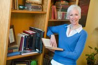 Cristen Iris holding a book and leaning against a bookcase promo image