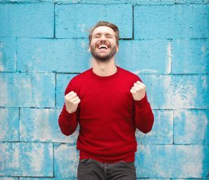 happy man in red sweater in front of blue wall