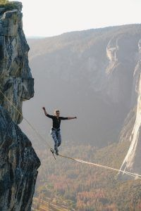 person walking a tightrope over a deep canyon