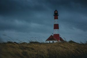 lighthouse on a grassy hill at dusk with a storm approaching