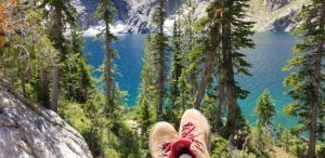 alpine lake in Sawtooth Mountains, Idaho in the background, hiking boots in the foreground