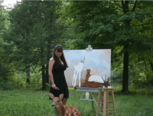author and painter JoAnne Helfert Sullam in a meadow with partially painted canvas of deer image with a live fawn looking on