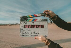 dirt road and field movie location in background, clap board in the foreground