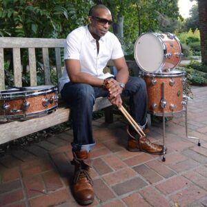 Billy Kilson sitting on a bench near drum kit while holding drum sticks