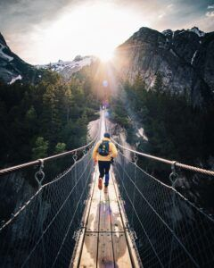 man on a foot bridge in rugged mountains